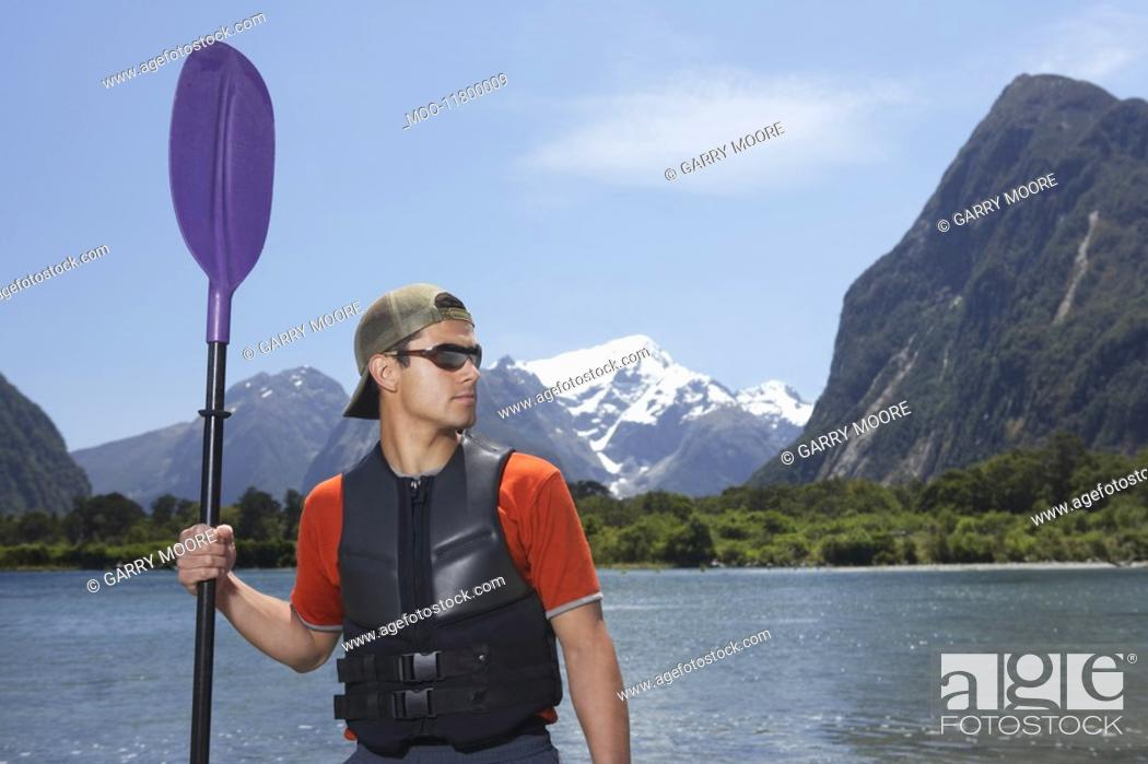 Stock Photo: Man holding oar on shore of mountain lake.