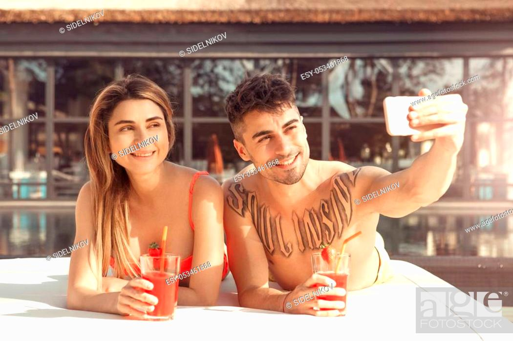 Stock Photo: Young man and woman rest together near swimming pool taking photos.