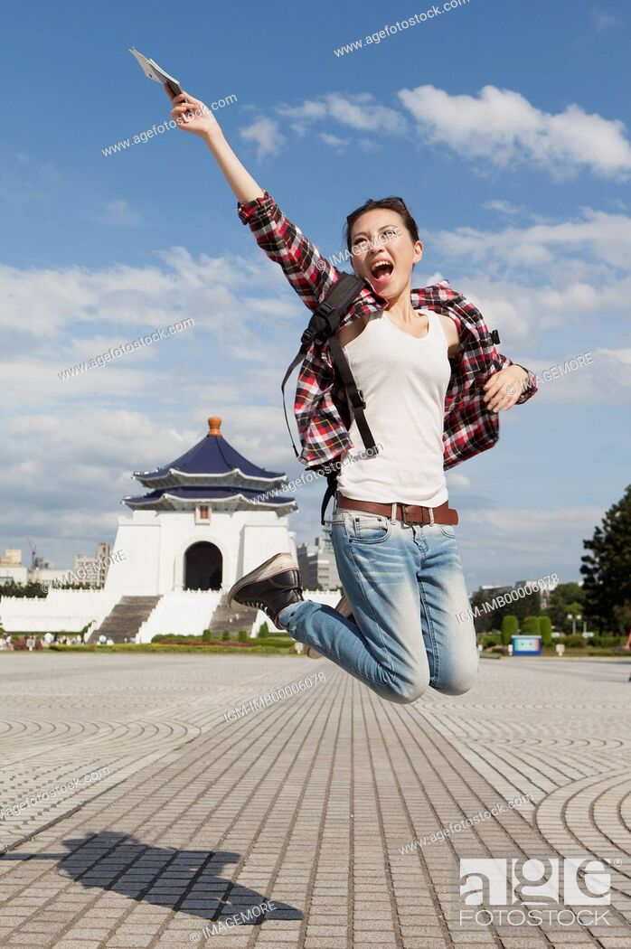 Imagen: Young woman jumping in mid-air and smiling happily,.