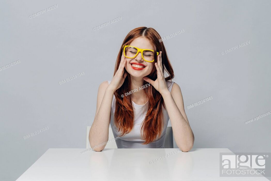 Stock Photo: Laughing Caucasian woman sitting at table wearing yellow eyeglasses.