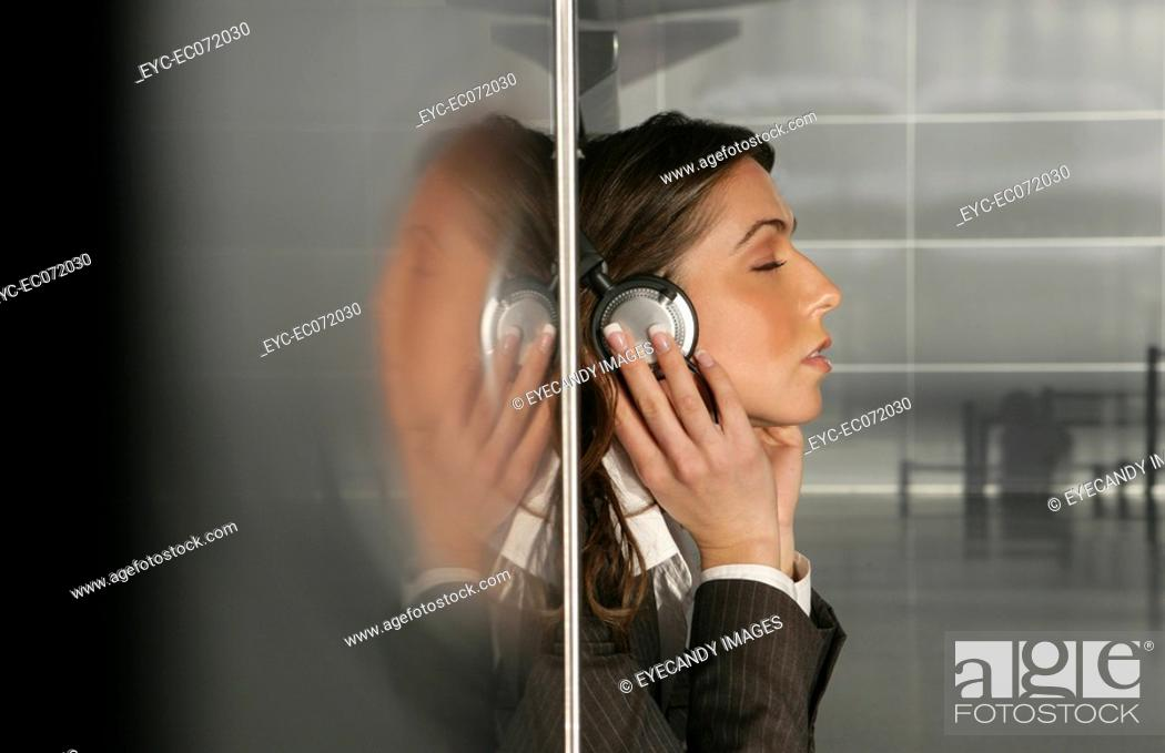 Stock Photo: Young businesswoman listening to headphones in airport.