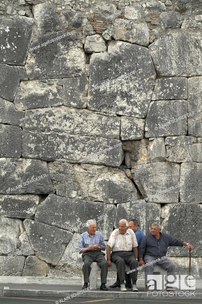 Stock Photo: Four senior men sitting on a bench in front of a stone wall, Amelia, Umbria, Italy.
