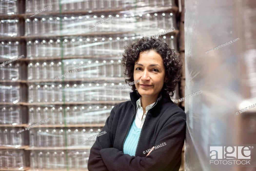 Stock Photo: Portrait of an African American female manager in a storage warehouse for pallets of flavoured bottled water.