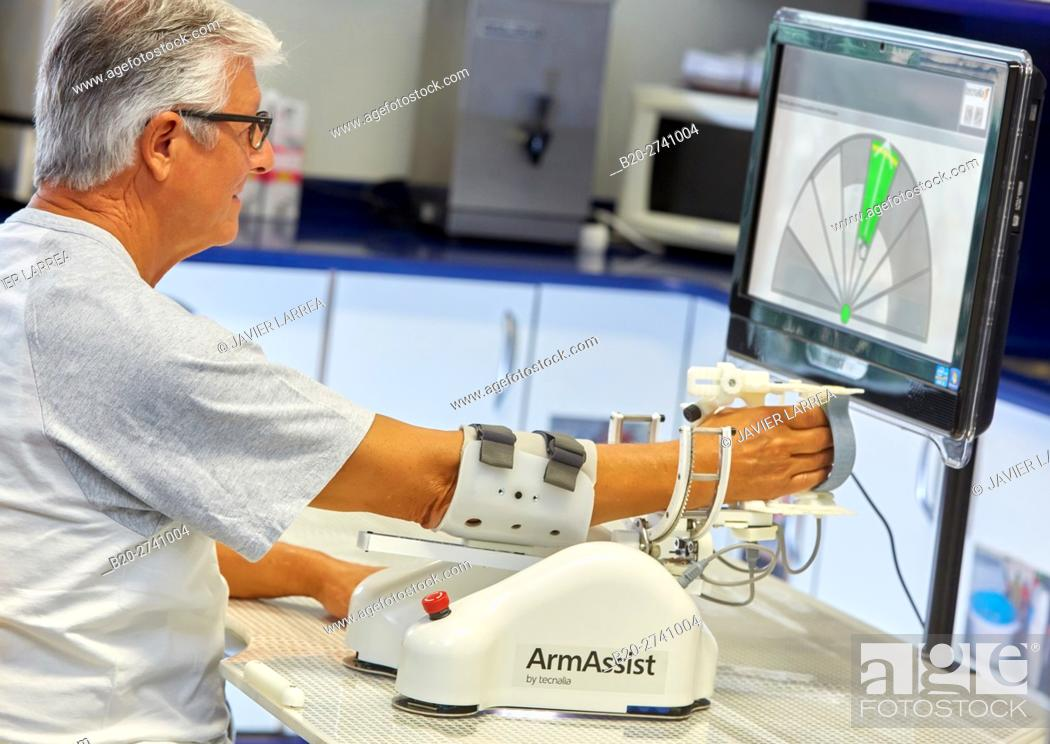 Stock Photo: Patient with assistive robot for upper limb rehabilitation, The robot ArmAssist allows passive, assisted and active training of the arm and hand.