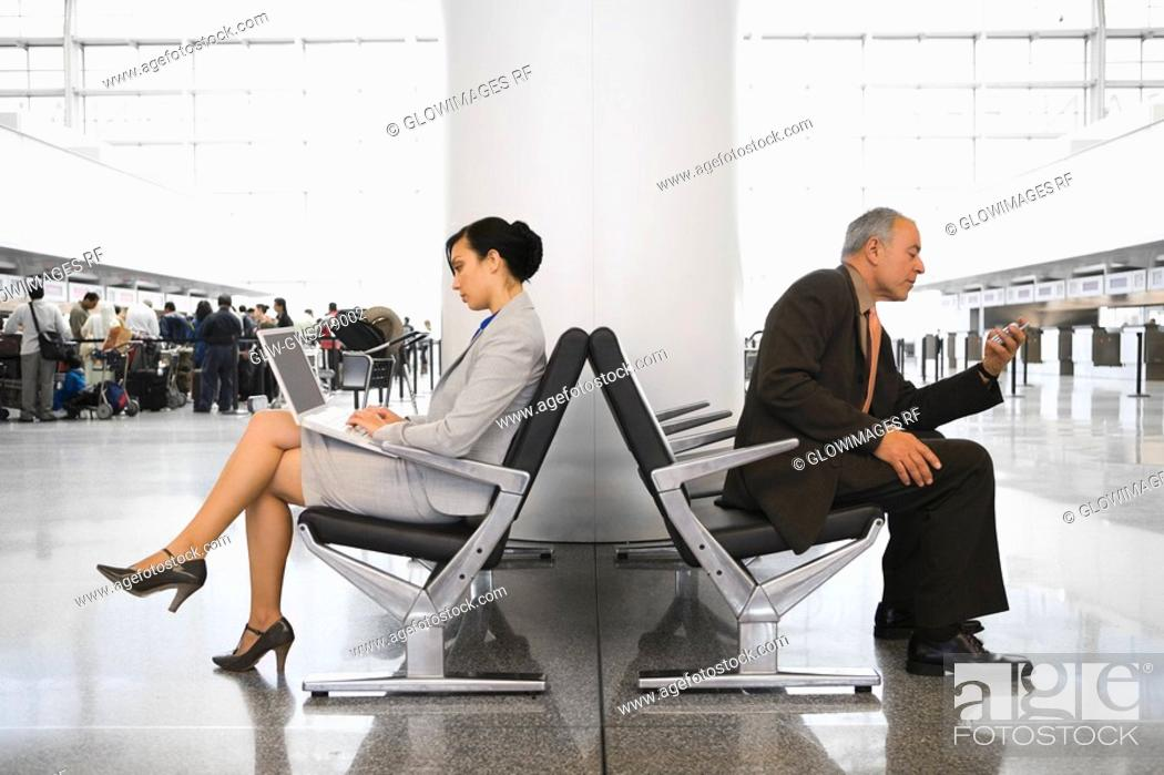 Stock Photo: Side profile of a businesswoman using a laptop and a businessman using a mobile phone at an airport.