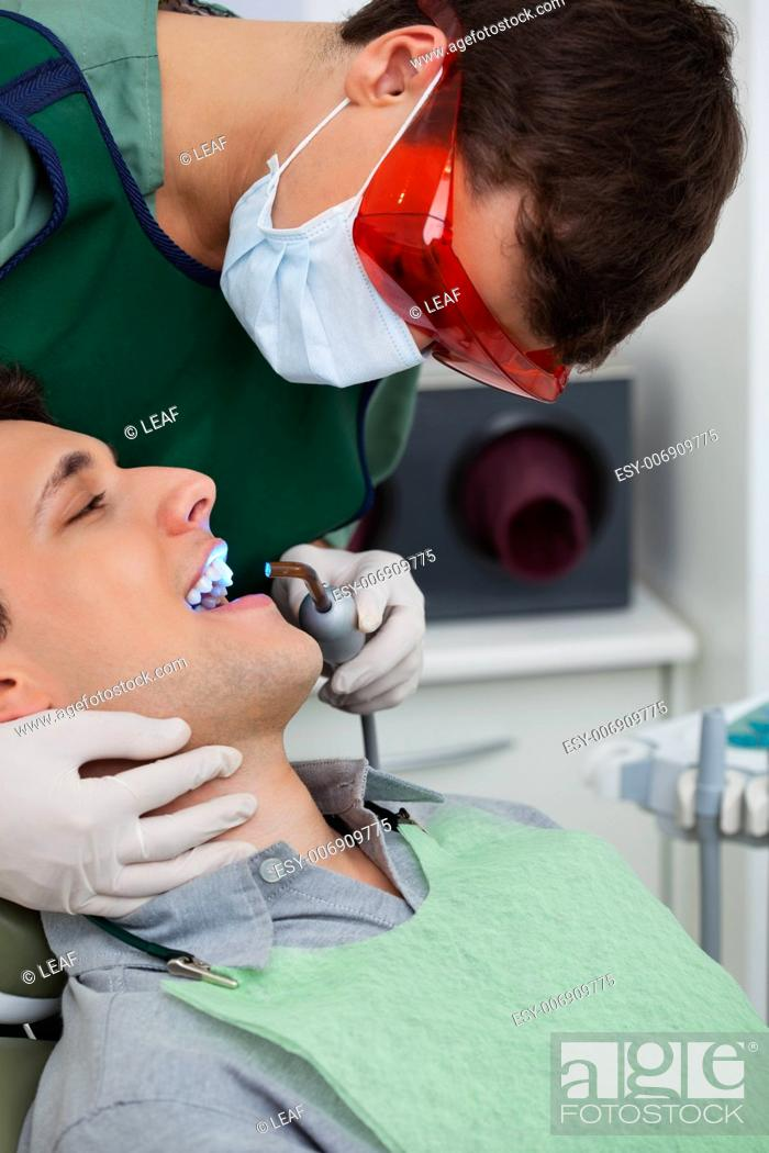 Stock Photo: Male orthodontist working on male patient with ultraviolet light.