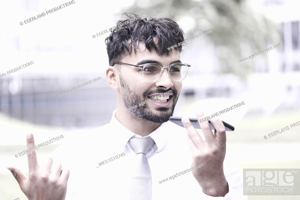 Stock Photo: optimistic businessman on the street, talking on phone, pointing up.