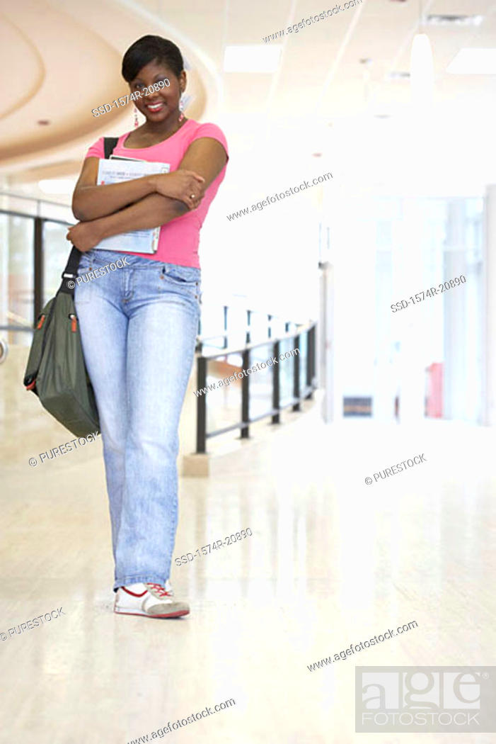 Stock Photo: Portrait of a college student standing in a corridor and smiling.