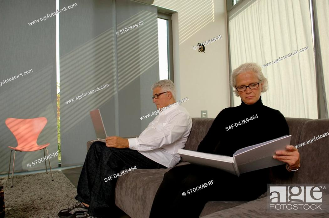 Stock Photo: Senior man with a laptop next to a senior woman with a book, both sitting on a settee.