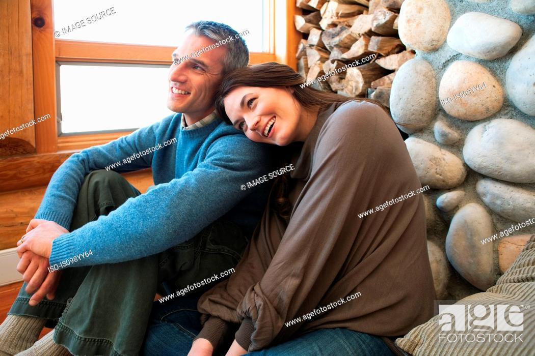Stock Photo: Mid adult couple sitting in log cabin.