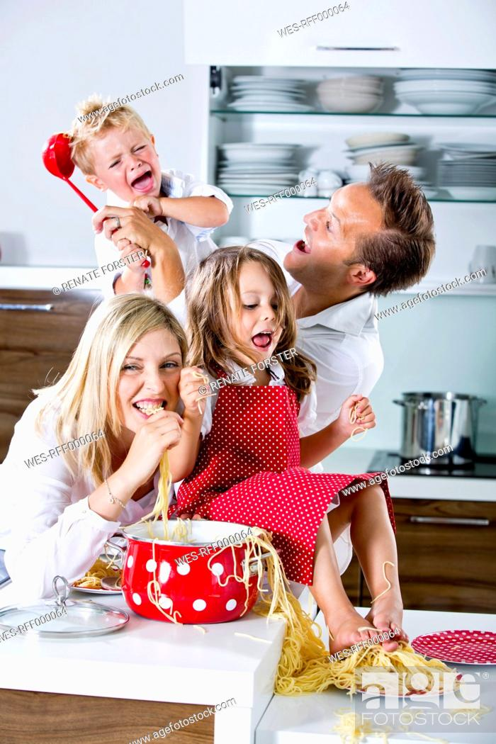 Stock Photo: Germany, Family playing with spaghetti on kitchen worktop.