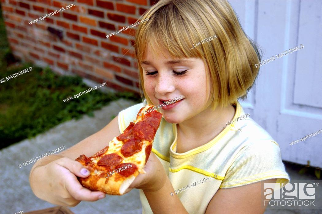 Stock Photo: Young girl eats pizza at a picnic.