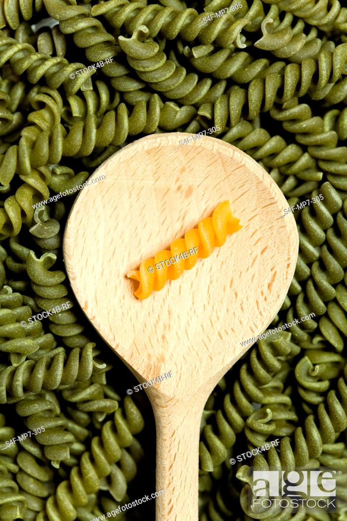 Stock Photo: Yellow noodle on wooden spoon amongst green noodles.