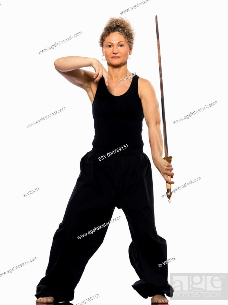 Stock Photo: mature woman praticing tai chi chuan with sword in studio on isolated white background.