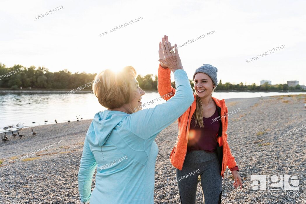 Stock Photo: Grandmother and granddaughter high-fiving after training at the river.