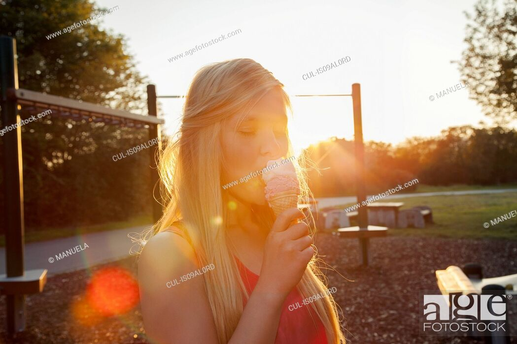 Stock Photo: Young woman eating ice cream cone in park at sunset.