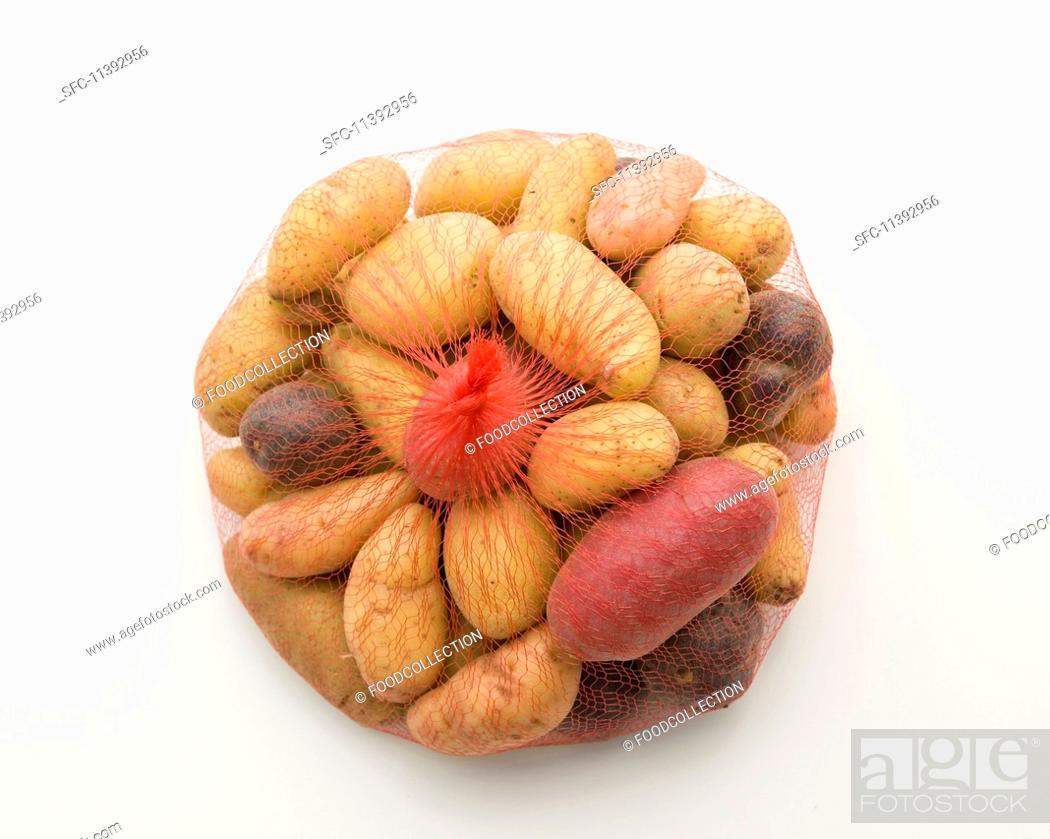 Photo de stock: Various heirloom potatoes in a net.