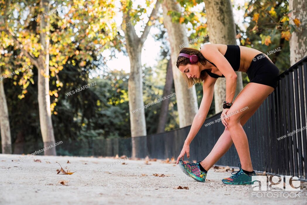 Stock Photo: Fit young woman stretching before training.