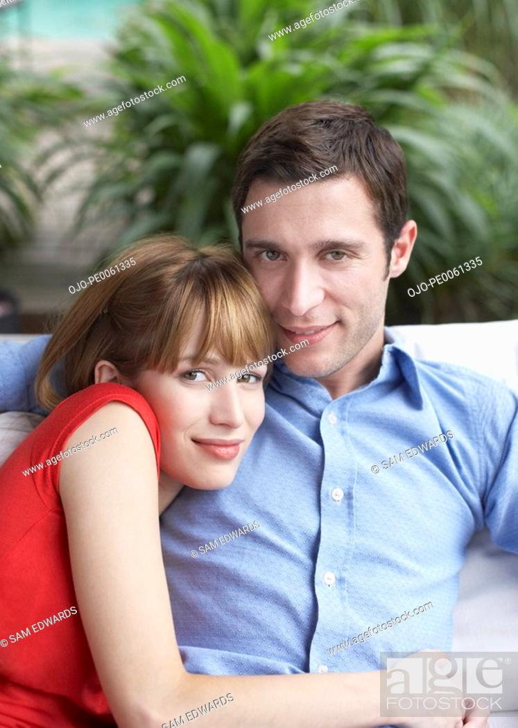 Stock Photo: Couple relaxing in living room smiling.