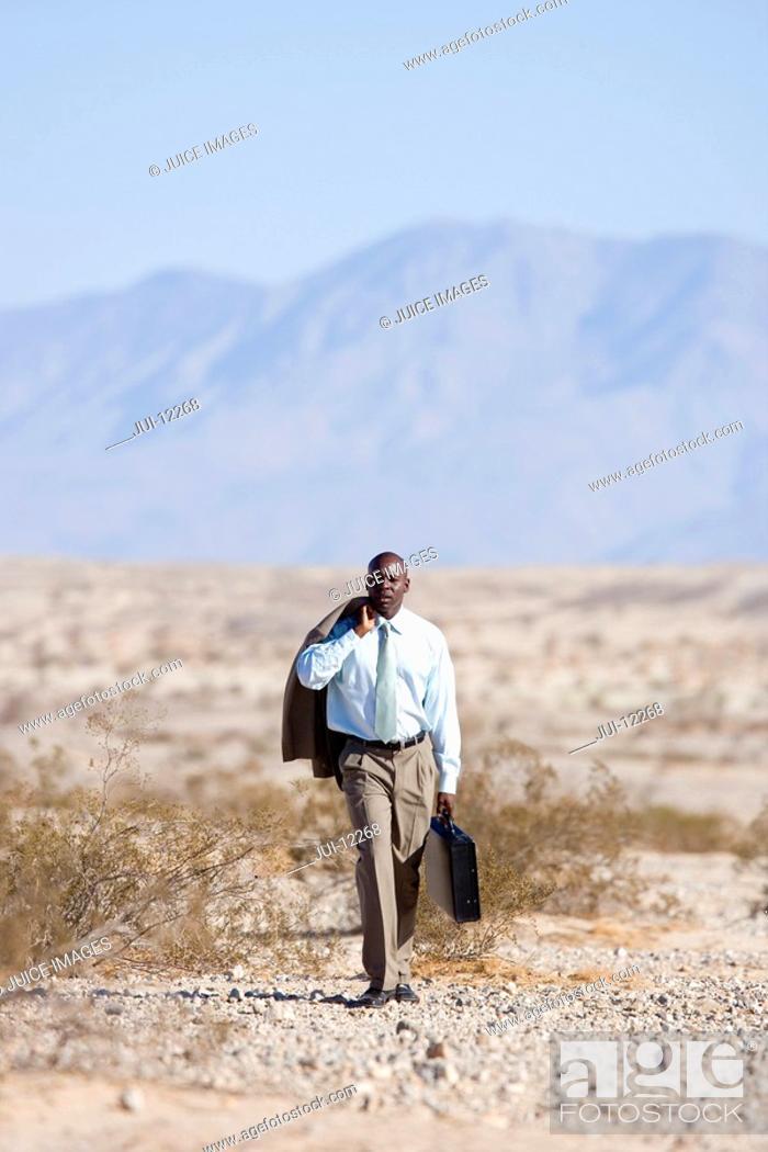 Stock Photo: Businessman with briefcase in desert, jacket over shoulder.
