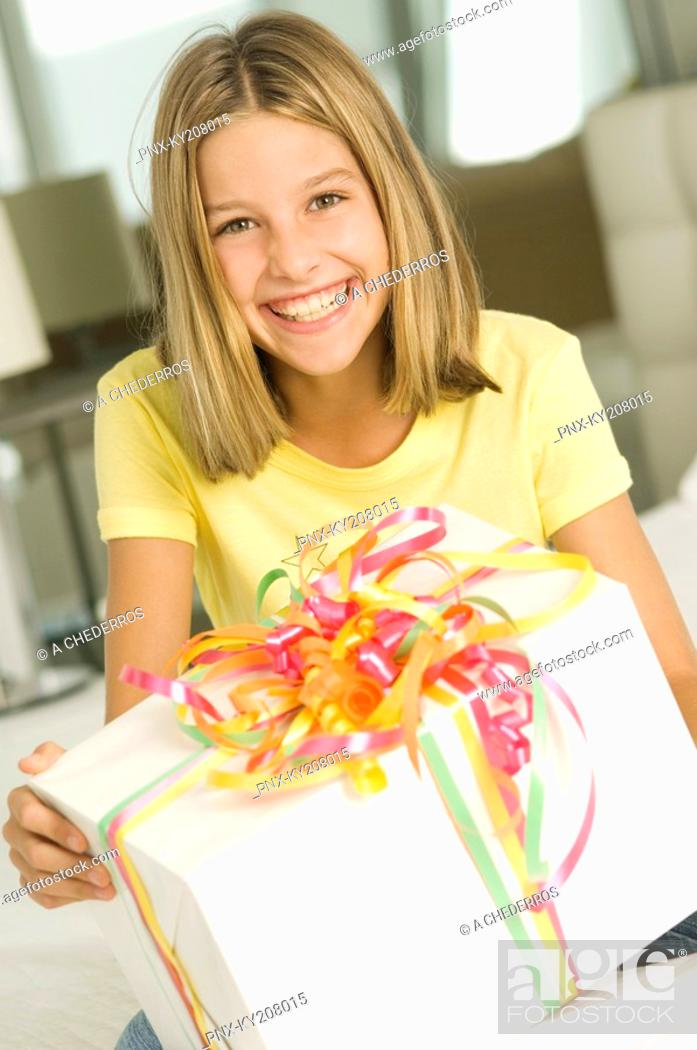 Stock Photo: Girl holding a birthday present and smiling.