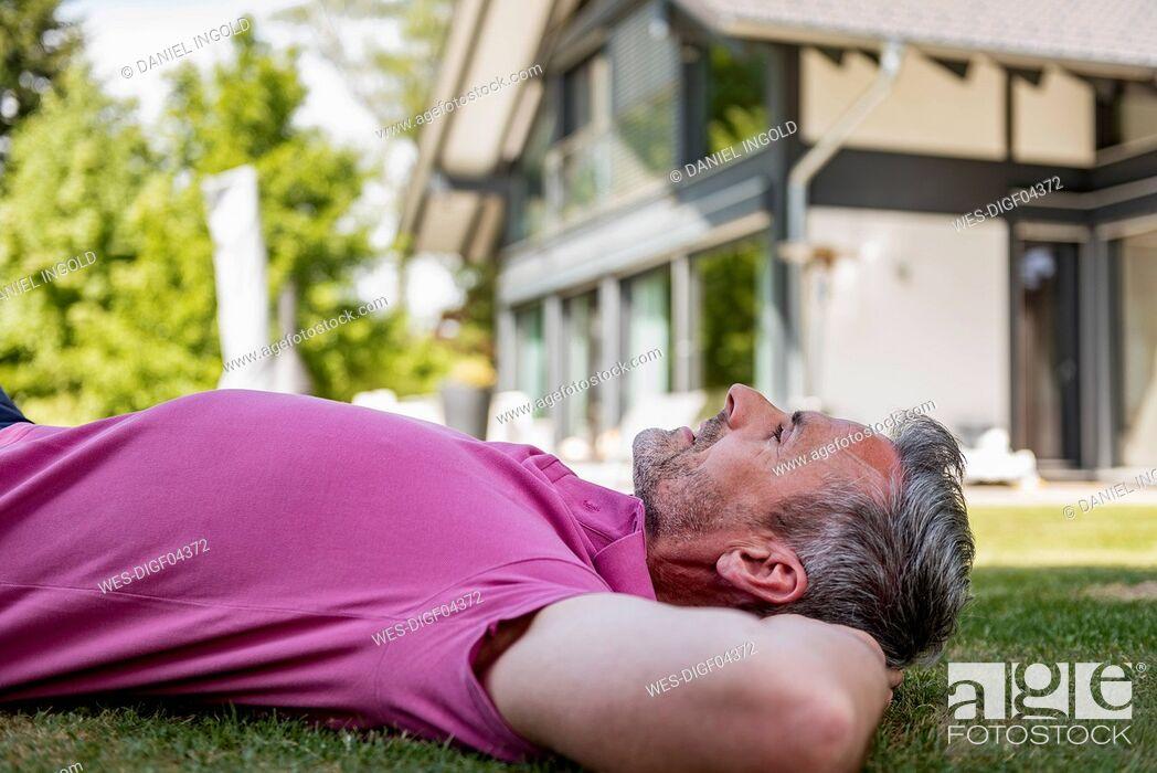 Photo de stock: Mature man lying in garden of his home.