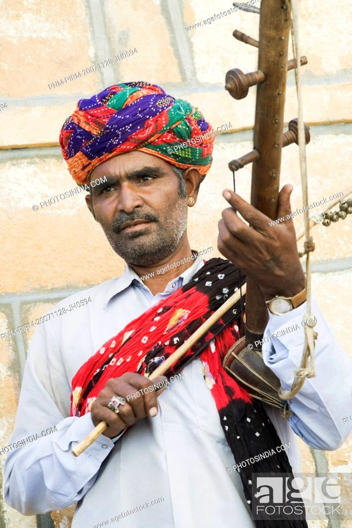 Imagen: Close-up of a musician playing a musical instrument, Jaisalmer, Rajasthan, India.