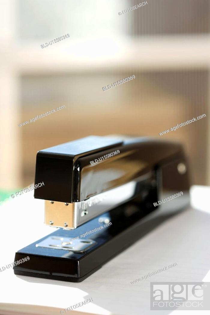 Stock Photo: Black stapler with window in background.