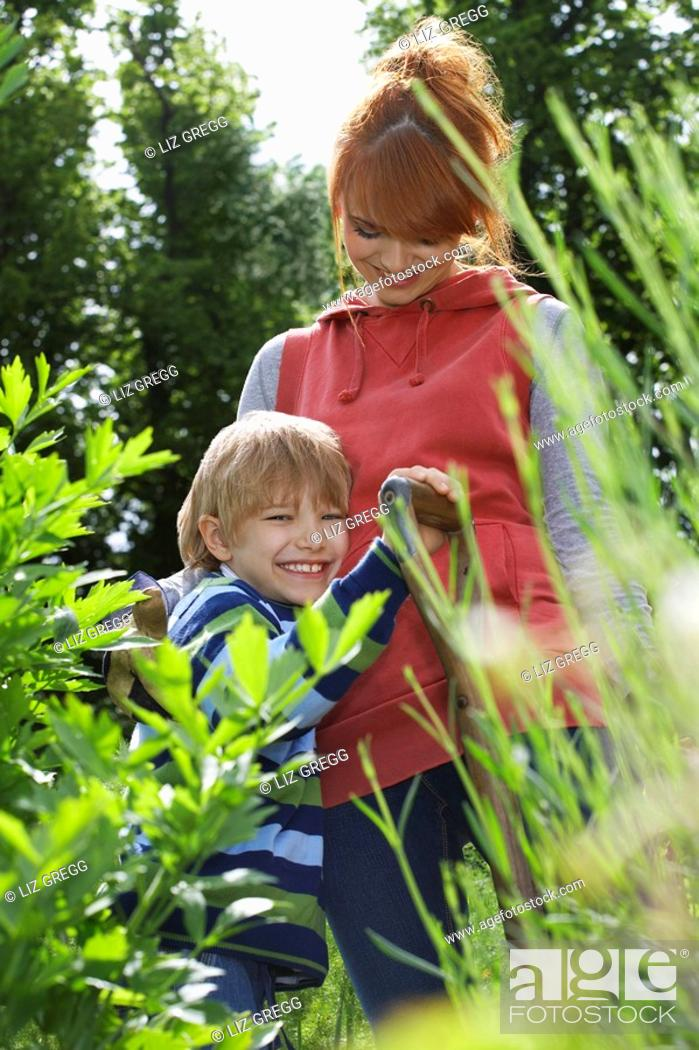 Stock Photo: Mother embracing son 5-6 in garden.