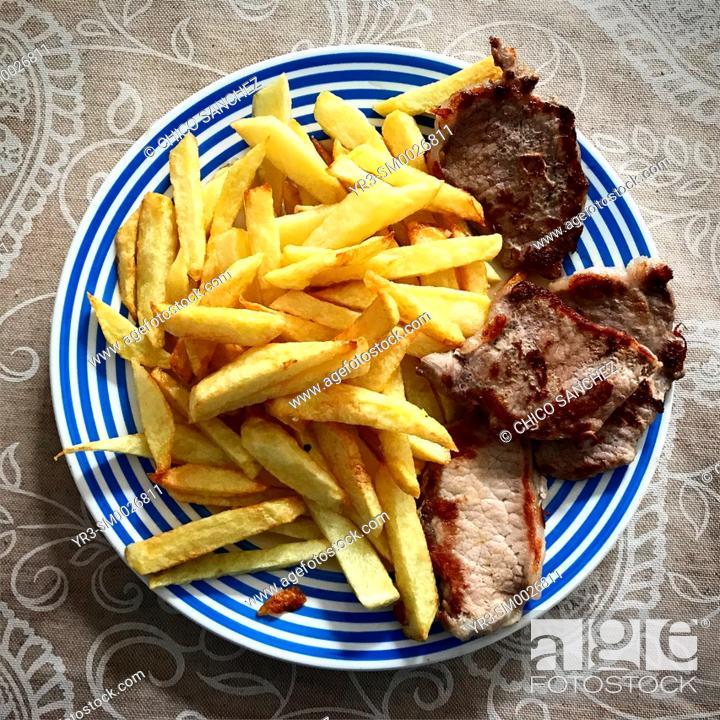 Stock Photo: Fried potatoes and Iberian pork in a home in Prado del Rey, Sierra de Cadiz, Andalucia, Spain.