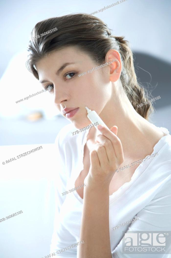 Stock Photo: woman applying face cream.