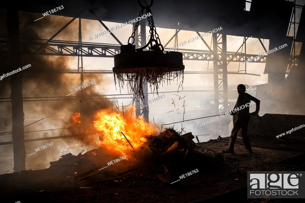 Stock Photo: Workers melt metal scraps in the furnace of a steel mill to produce rods in Demra, Dhaka, Bangladesh.