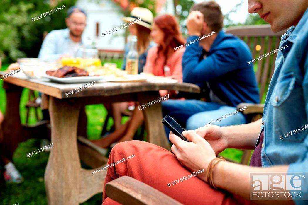 Stock Photo: leisure, holidays, people and technology concept - young man texting on smartphone and friends having dinner at summer garden party.