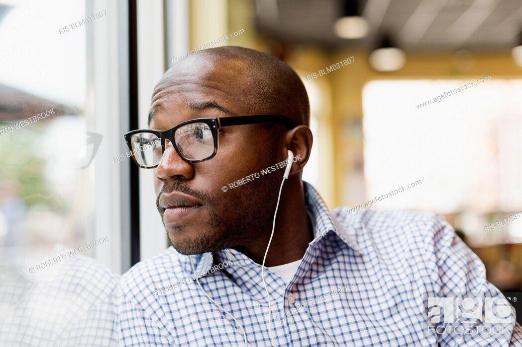 Imagen: Black man listening to earphones in coffee shop.