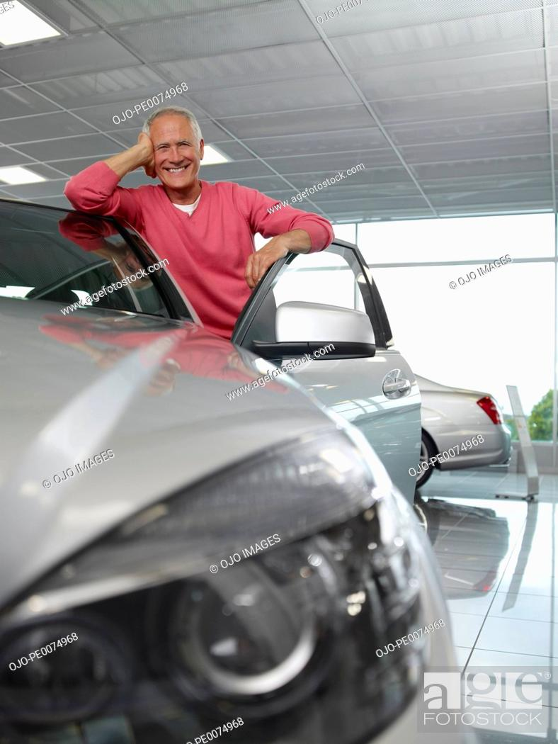 Stock Photo: Man looking at new car in showroom.