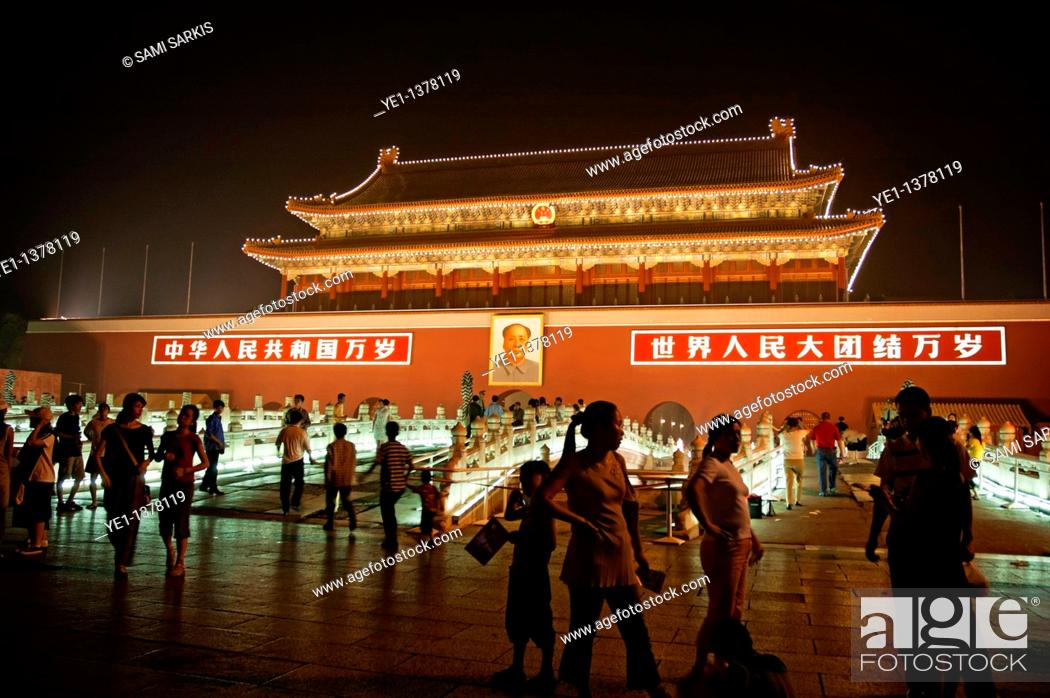 Stock Photo: People passing by a portrait of Mao Zedong on the Temple of Heavenly Peace at night, Tiananmen Square, Beijing, China.