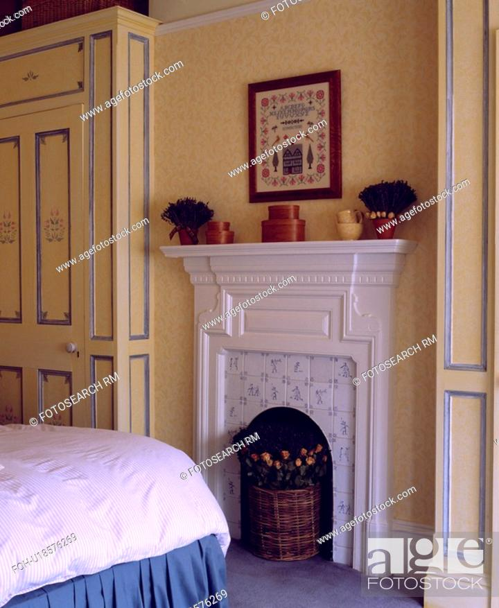 Stock Photo White Fireplace In Small Bedroom With Ed Wardrobes Blue Decorative Detail And Neutral Patterned Wallpaper