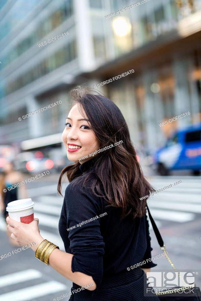 Stock Photo: USA, New York City, Manhattan, portrait of smiling young woman with coffee to go crossing the street.