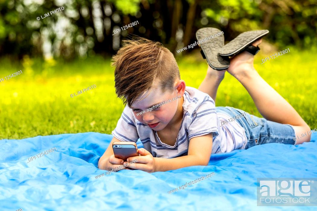 Stock Photo: A young boy playing with a smart phone and texting while laying on a blanket in a city park on a warm summer day; Edmonton, Alberta, Canada.