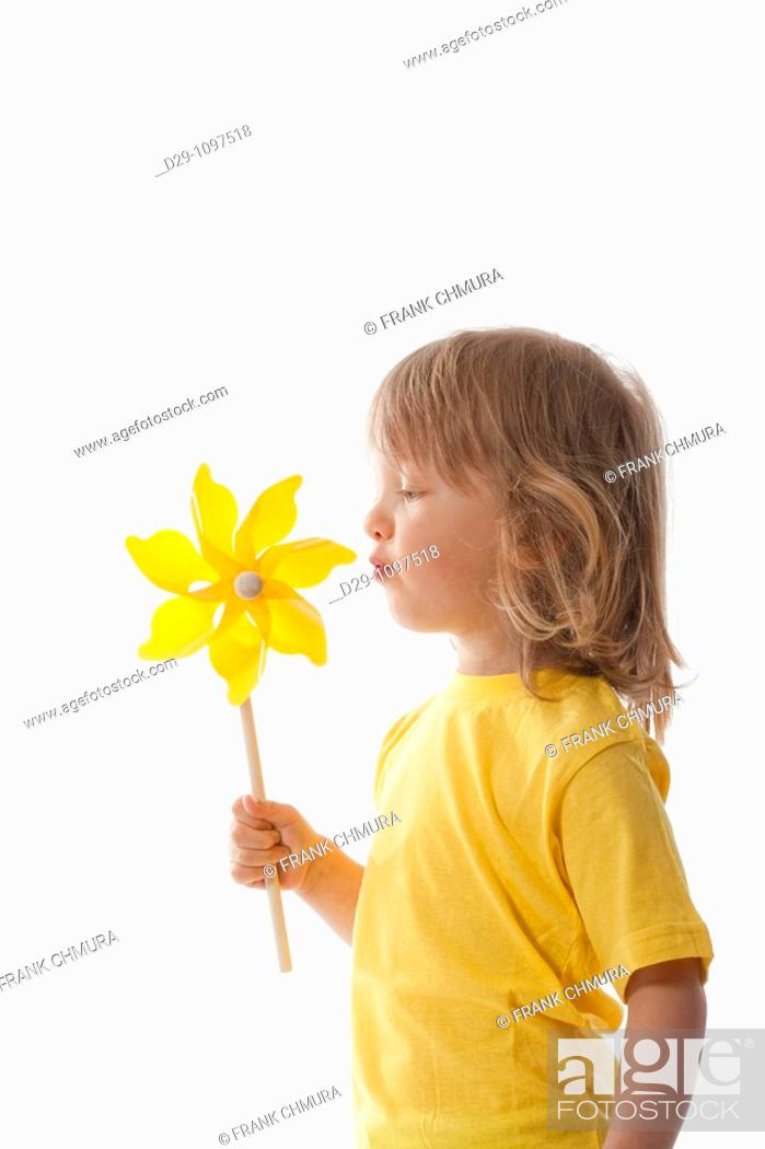 Stock Photo: studio shot of a boy playing with pinwheel - isolated on white.