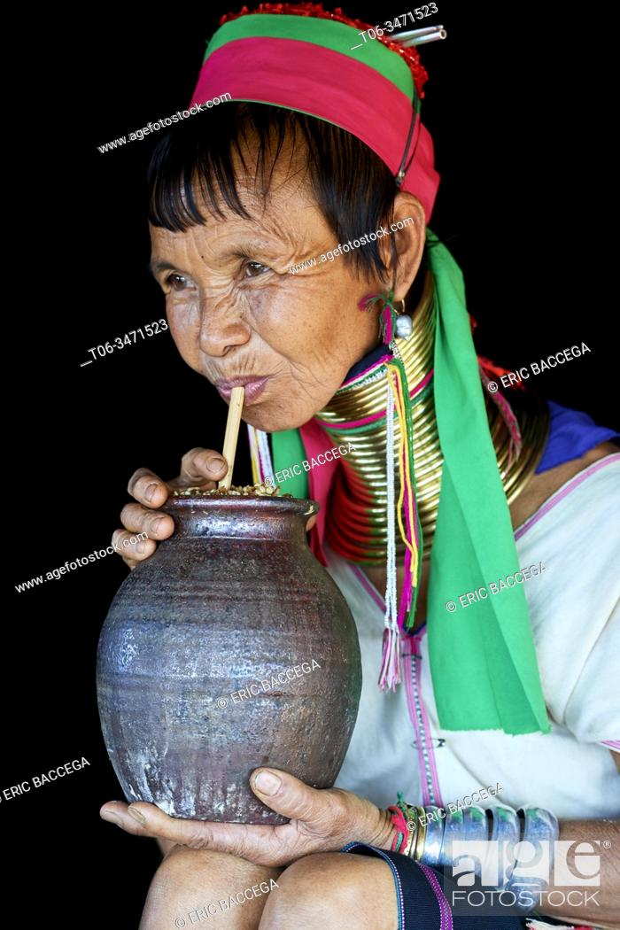 Stock Photo: Kayan Lahwi woman with brass neck coils and traditional clothing and drinking a liquor distilled from fermented sorghum, a very common drink among Kayan.