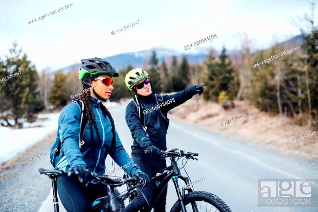 Imagen: Two mountain bikers riding on road outdoors in winter, talking.
