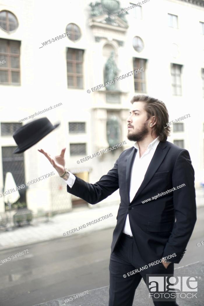 Stock Photo: stylish man throwing hat in air.