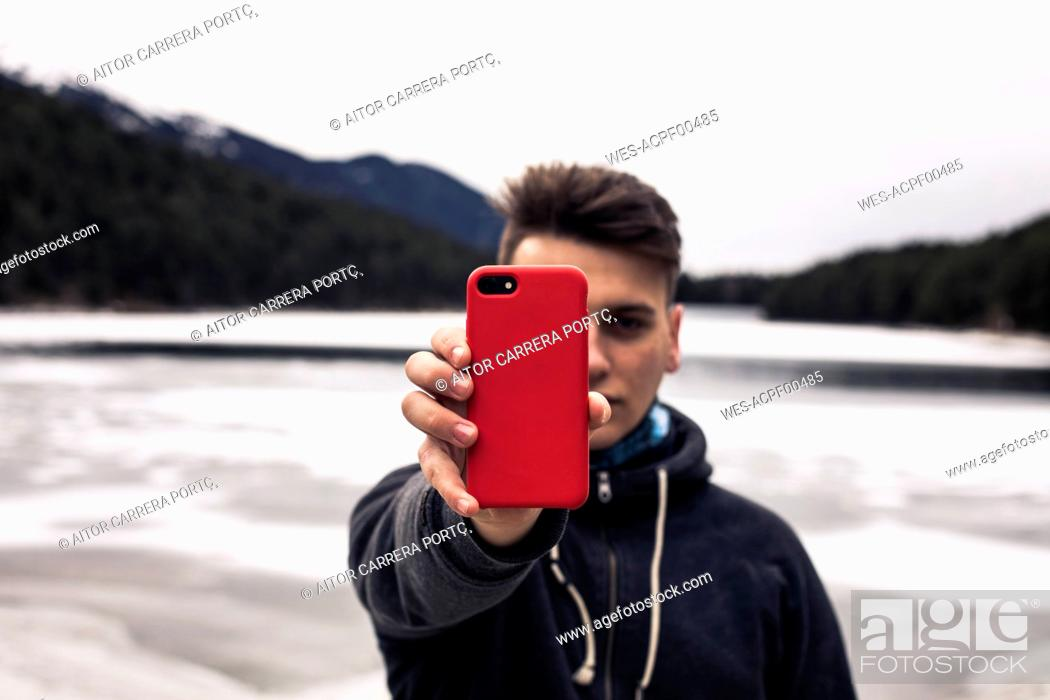 Stock Photo: Young man holding red cell phone at a lake in winter.