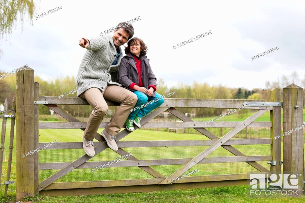 Stock Photo: Man sitting with his son on the gate of a cottage.