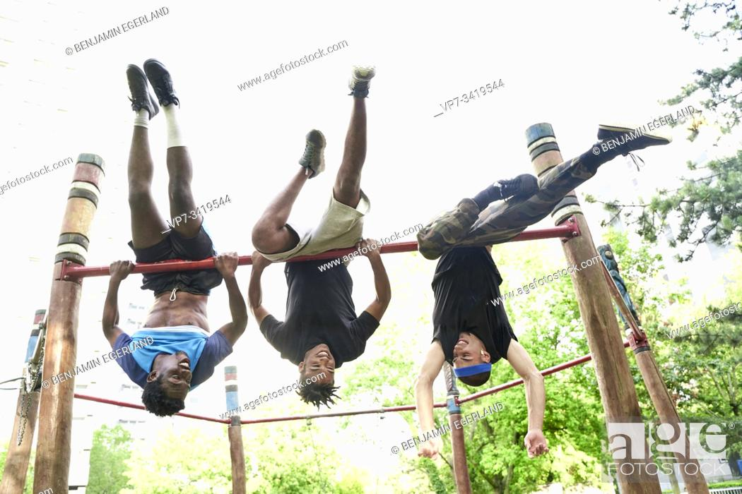 Stock Photo: Young men doing acrobatics in park. Frankfurt am Main, Germany.