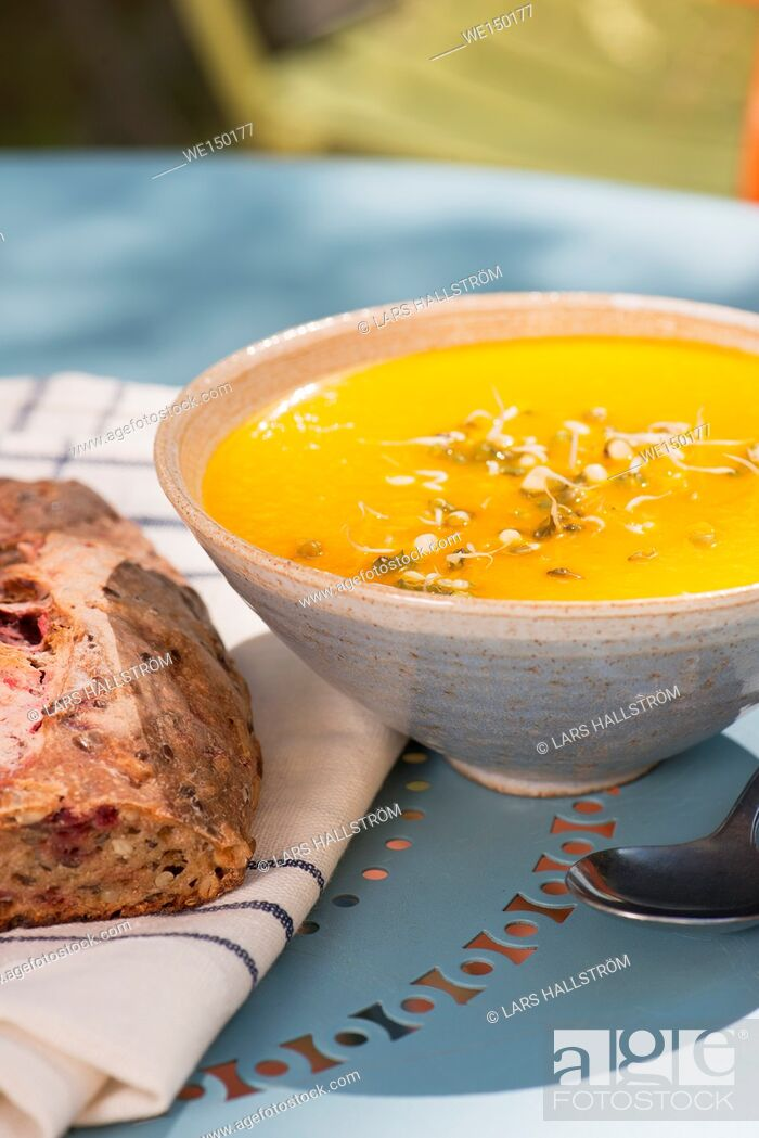 Stock Photo: Bowl of hot carrot and ginger soup served with freshly baked bread. Colorful food.