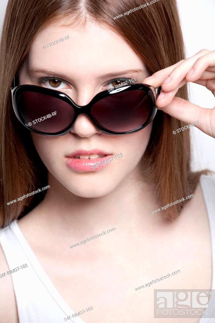 Stock Photo: Brunette young woman wearing sunglasses.