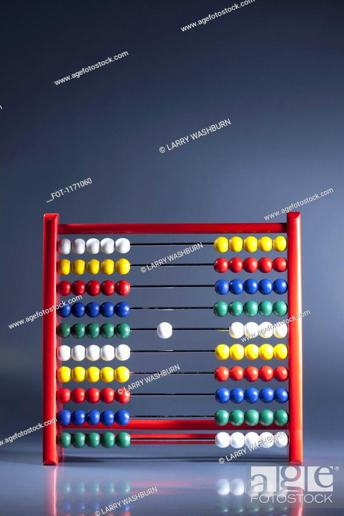 Stock Photo: An abacus with neat rows of multi colored beads and a single white bead in the middle.