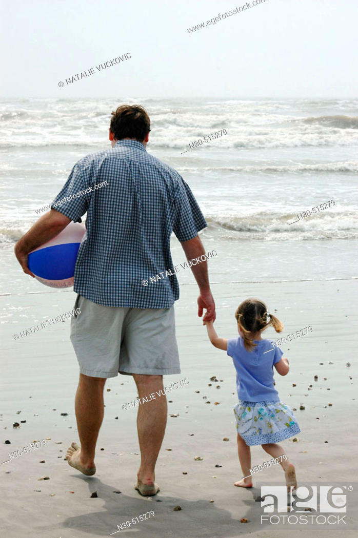 Stock Photo: Rear view of father and daughter walking on beach.